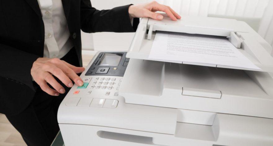 Person hitting start button on copier